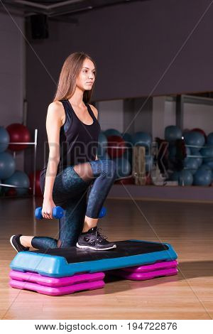 fitness, sport, training, gym and lifestyle concept - woman stepping with dumbbells on step platform in gym.