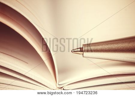 selective focus of the ball pen on opened lined diary book vintage retro color tone