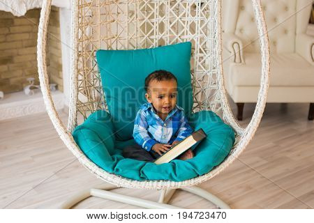 Portrait of African American baby boy holding book on sofa.