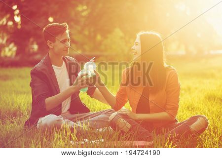 A loving couple of teenagers. Sudden picnic in the park at sunset. Teenagers are drinking cold drinks while sitting on the lawn.