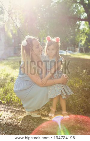 Family values. Mother and daughter. Same dresses and hairstyles. Backlight of the setting sun. Family look