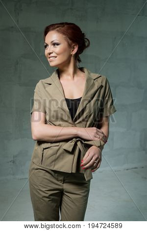 Beautiful red haired woman in nice khaki jacket and pants studio portrait