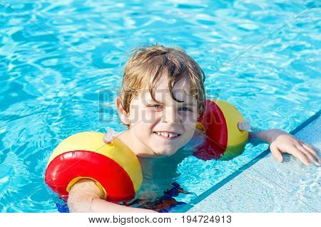 Happy little kid boy having fun in an swimming pool. Active happy child learning to swim. with safe floaties or swimmies. Family, vacations, summer concept.