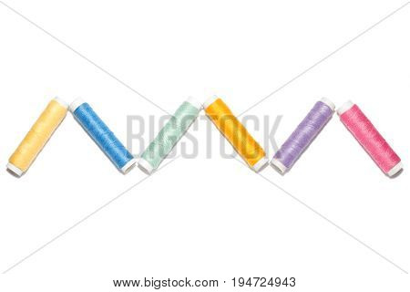 Zigzag of colorful thread spools for sewing or embroidery isolated on white background, horizontal
