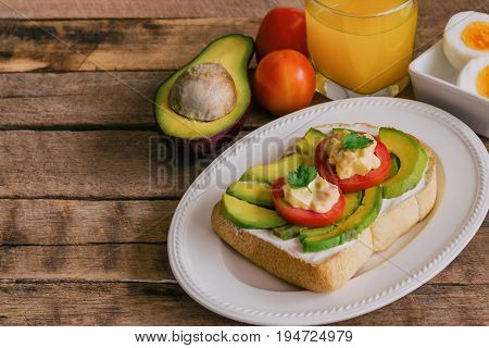 Open sandwich for breakfast or lunch. Sandwich spread with cream cheese avocado tomato and boiled eggs on white plate. Avocado open sandwich serve with orange juice on wood table with copy space. Delicious homemade sandwich ready to served.