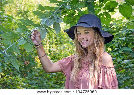 smiling pretty teenage girl wearing black hat in summer woods