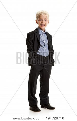 Full portrait of cheerful little boy in school uniform holding hands in pockets