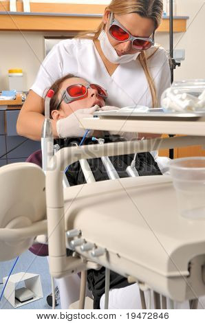 Female dentist whitening teeth with multi purpose laser - a series of DENTAL related images.