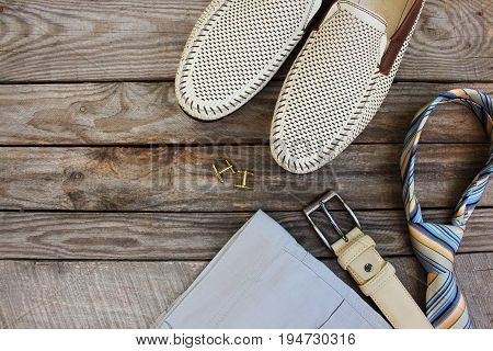 Men's clothing and accessories on wooden background. Top view.