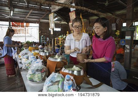 mahasarakham thailand - july82017 : thai woman drop sticky rice to buddha monk food container at temple early morning on asalha puja day important buddhist day