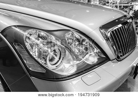 STUTTGART GERMANY - MARCH 17 2016: Headlamp of full-size luxury car Maybach 57S 2006. Black and white. Europe's greatest classic car exhibition