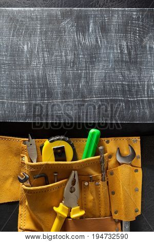 tools and instruments in belt on black background