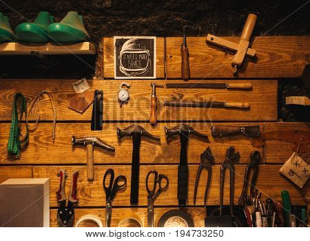 Picture of instruments on wooden wall at footwear workshop.