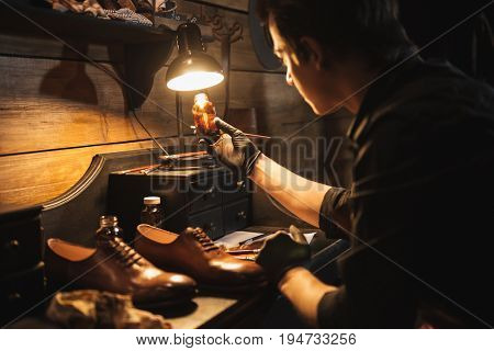 Picture of young concentrated man shoemaker at footwear workshop.