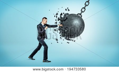 A businessman in full height punching and breaking a huge wrecking ball on blue background. Crisis management. Problem solving. Fight adversary.