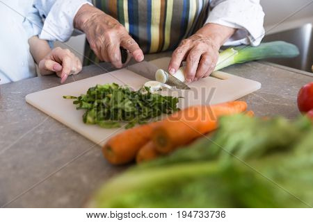 Close up of a senior lady cutting vegetables on a board with her granddaughter at the kitchen