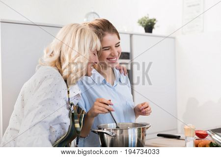 Happy grandmother and granddaughter hugging while stirring soup with a spoon at the kitchen at home