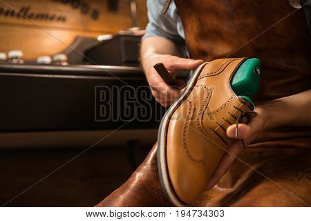 Cropped image of young shoemaker in workshop making shoes.