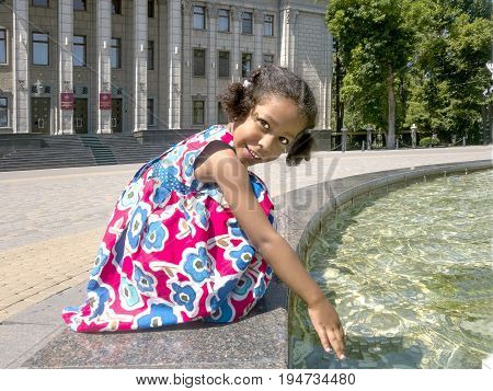 Happy fashionable smiling mixed ethnicity little girl in elegant dress wetting her hand in a fountain. A child, daughter of a Russian mother and a Jamaican father, for a walk in the city during the summer vacation