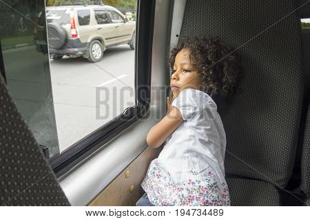 Thoughtful and serious little girl looking out the window in the bus. Small tired and sad female mixed ethnicity child with curly hair sitting on the bus chair