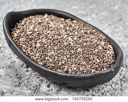 Close up view of chia seeds in trendy plate with copy space. Chia seed on gray concrete textured background. Healthy food and diet concept