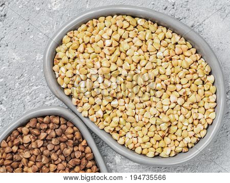 Close up view of raw green buckwheat in trandy plate and brown roasted buckwheat on background. Healthy food and diet concept. Top view or flat lay