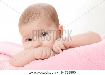 the little beautiful baby lies on a blanket