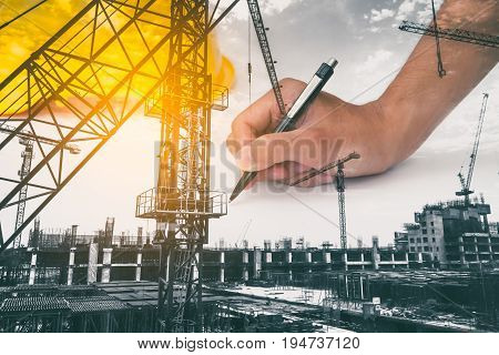 Double exposure of architect working on blueprint with construction site.