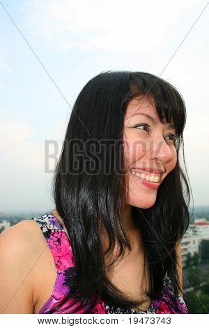 Asian girl under a cloudy sky.