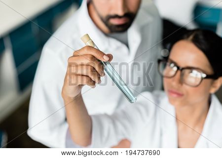 Close-up View Of Colleagues In White Coats Examining Test Tube With Reagent In Chemical Lab