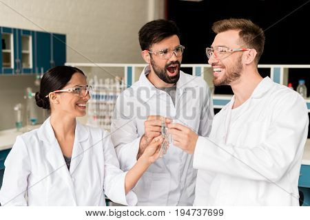 Cheerful Young Chemists Clinking Test Tubes With Reagents In Lab