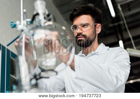 Concentrated Bearded Scientist In Protective Eyewear Making Experiment In Laboratory
