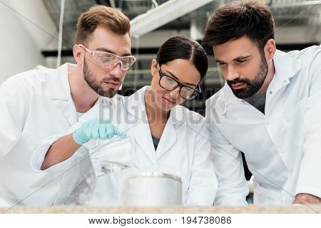 Team Of Professional Scientists In Lab Coats Making Chemical Experiment Together