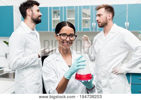 Smiling Young Chemist Holding Flask With Reagent While Colleagues Talking Behind In Lab