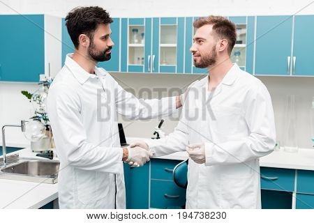 Professional Young Chemists In White Coats Shaking Hands In Scientific Laboratory