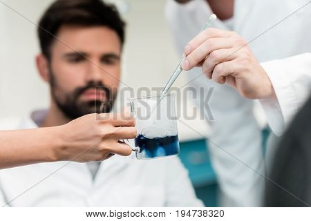Close-up view of scientists making experiment with reagent and pipette