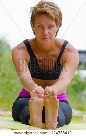 Hatha yoga. Paschimottanasan. Yoga poses, asan. Titl to feet. Concept of healthy life. Practicing yoga, sitting in Head to Knee Forward Bend exercise, Janu Sirsasana pose, wearing sportswear, bra