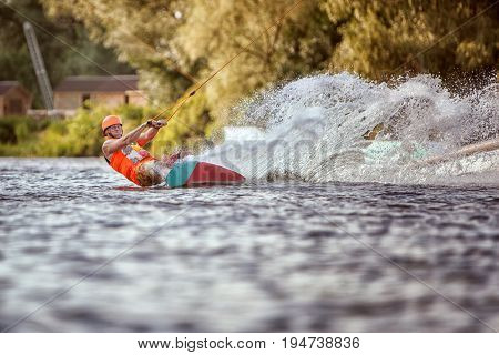 Man goes for a drive on wakeboarding around splashes of water.