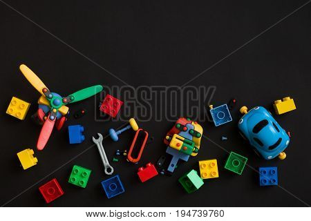 Colorful plastic bricks cars and details of toys on black paper background. Parts of bright small spare parts for toys.