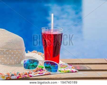 sun glasses hat and red soft drink with at the side of swimming pool. Vacation beach summer travel concept