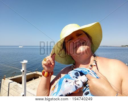Portrait of a sunburnt woman standing on a pier holding a hat in the wind