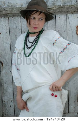 Woman in a hat and national folk dress embroidered standing near a fictitious wall in beads