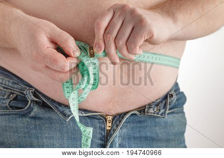 Fat man holding a measurement tape on belly