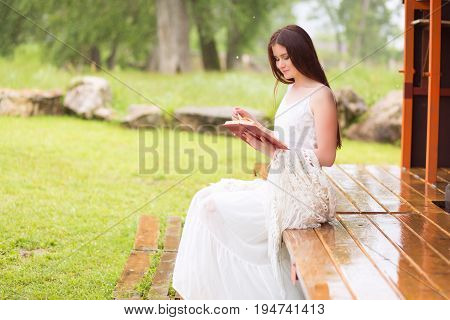 Beautiful Young Woman Reading A Book Outdoor. Sitting On Terrace Or On Porch