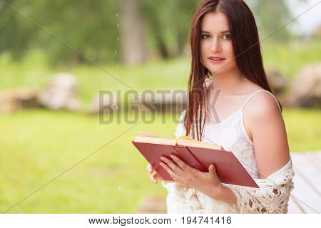 Attractive Young Girl Reading Book In White Dress