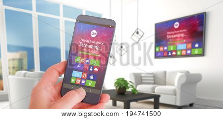 Female hand holding a smartphone against white sofas in modern living room