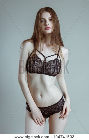 Slender long-haired girl in a beautiful lace underwear of black color