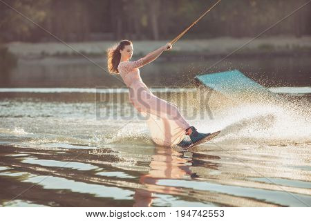 Pretty woman riding a wakeboard on the lake in the park.