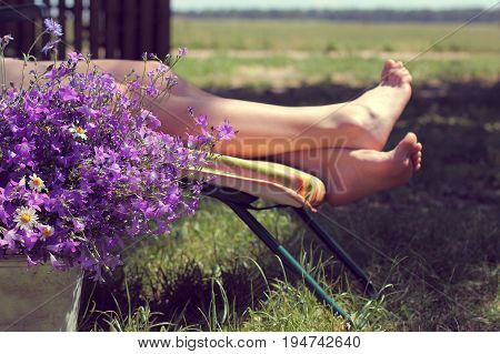 large bouquet of wildflowers on a background of unrecognizable woman on a deck chair at summer day / rest on vacation in the village
