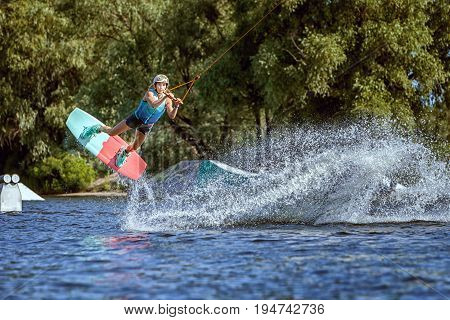 Professional sportswoman in training on wakeboarding. She jumps on the water on the board.